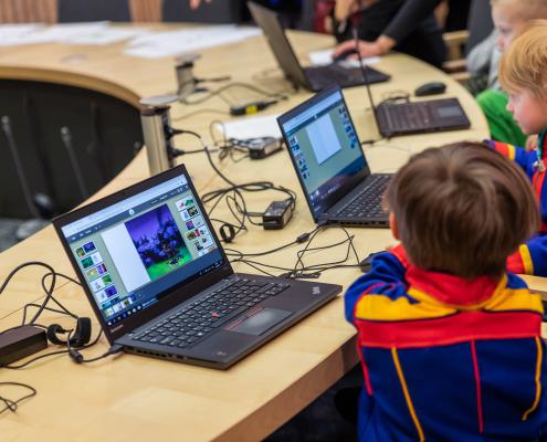 Kaksi poikaa tekee kannettavalla tietokoneella tehtäviä pöydän ääressä.