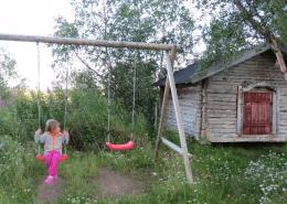Lapsi keinuu keinussa ulkona kesällä.
