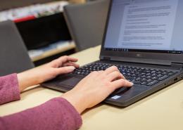 Kädet kannettavan tietokoneen näppäimistöllä.
